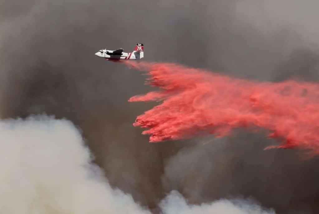 plane dumping water on fire during aerial firefighting mission