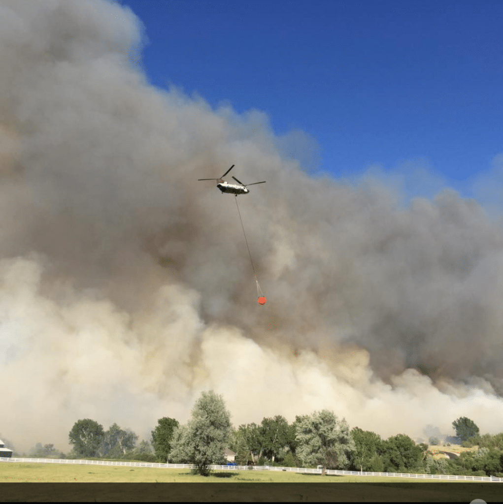 CH-47D Chinook helicopter flying above a wild fire carrying water bucket