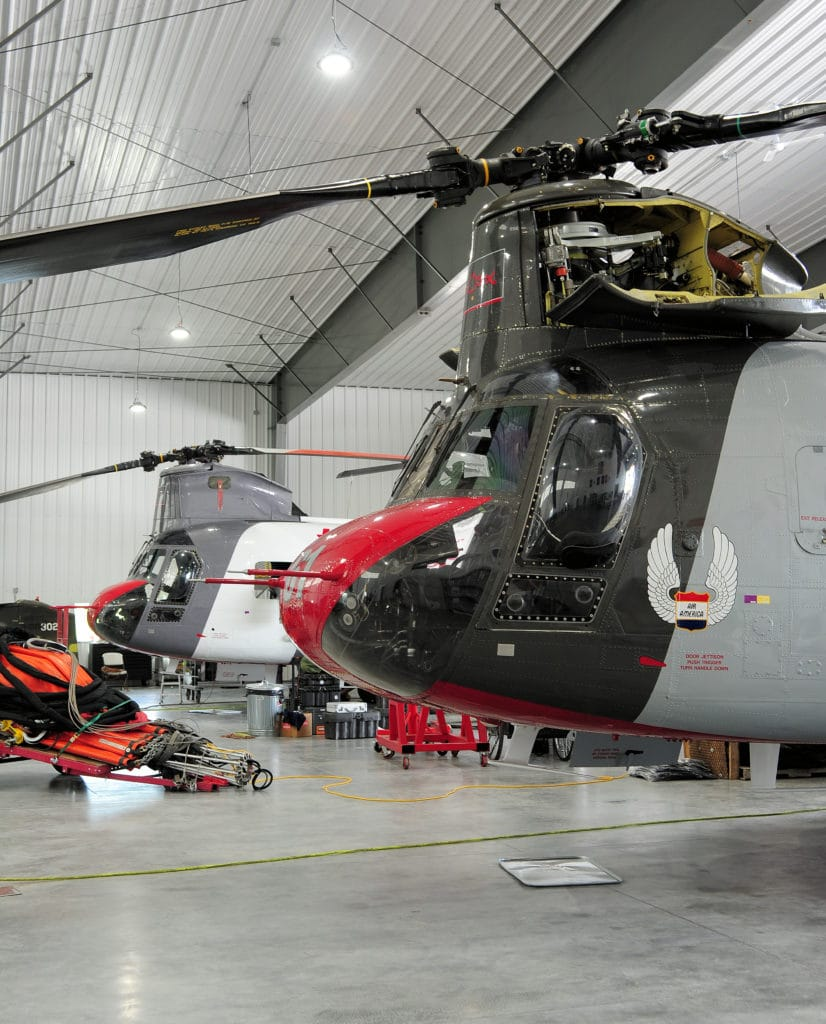 Chinooks in hanger being serviced by crew