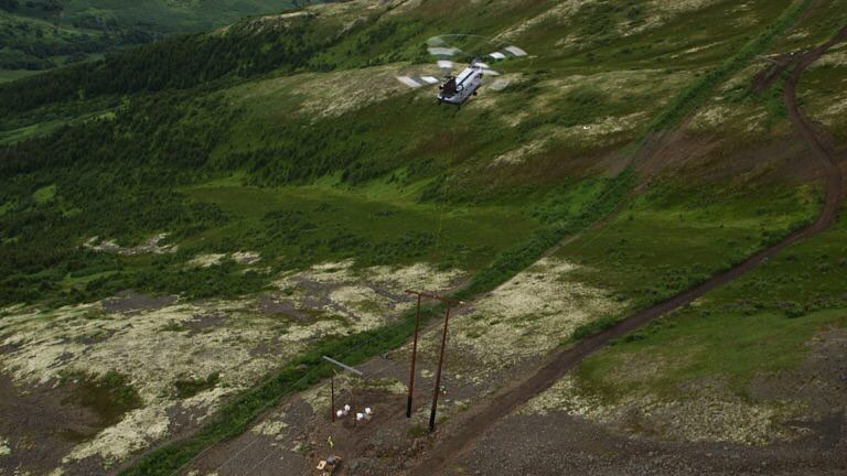 CH-47D Chinook Helicopter heavy lift mission lifting power line on construction site
