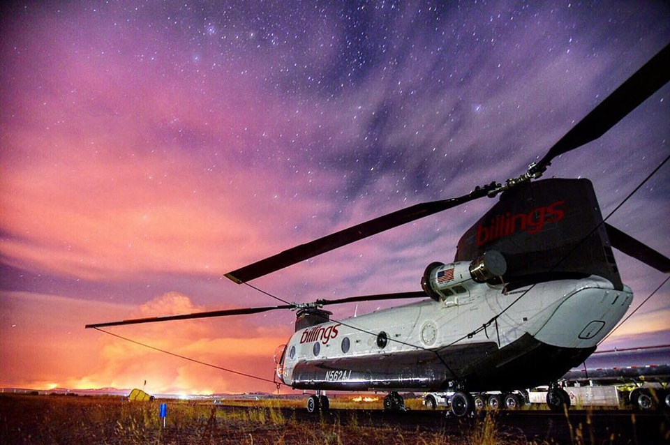 CH-47D at dusk with wildfire in distance