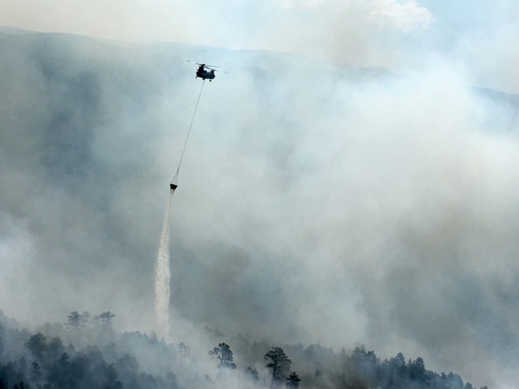 chinook helicopter fire fighting dumping water bucket over wildfire